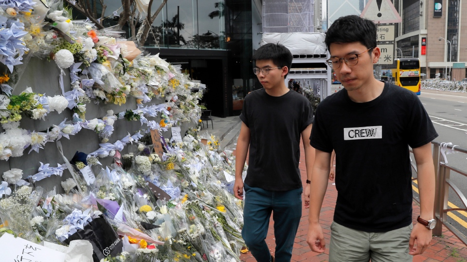 Pro-democracy activist Joshua Wong, left, is accompanied by Nathan Law as they arrive at a makeshift memorial to a pay respect to a protester who fell to his death after hanging a protest banner against an extradition bill in Hong Kong, Monday, June 17, 2019. (AP Photo/Kin Cheung)