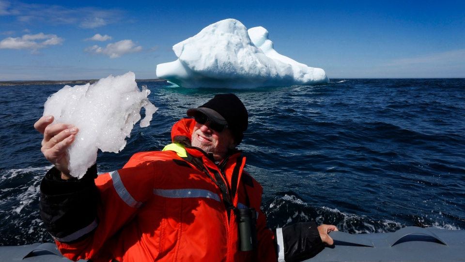 Tourist, Jim East of Florida, collects a piece of Iceberg ice during an Iceberg tour with Trinity Eco-Tours in Bonavista Bay, Newfoundland and Labrador on Tuesday, June 11, 2019. (THE CANADIAN PRESS/Paul Daly)