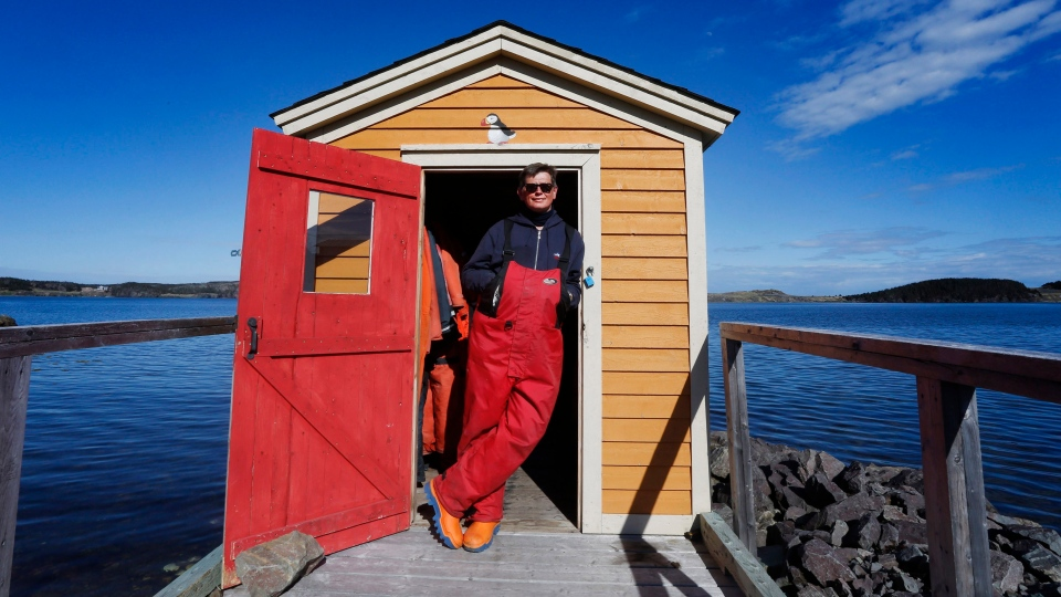 Skipper Bob Bartlett of Trinity Eco-Tours, Trinity N.L. poses for a picture in front of his shed of survival suits, prior to leading an Iceberg tour in Bonavista Bay on Tuesday, June 11, 2019. (THE CANADIAN PRESS/Paul Daly)