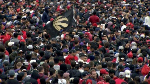 A Toronto Raptors flag is seen amongst a crowd of waiting fans ahead of the victory parade on June 17, 2019.