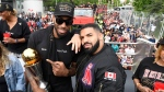 Toronto Raptors forward Kawhi Leonard points at his playoffs MVP trophy as he poses with performing artist Drake during the 2019 Toronto Raptors Championship parade in Toronto on Monday, June 17, 2019. THE CANADIAN PRESS/Frank Gunn