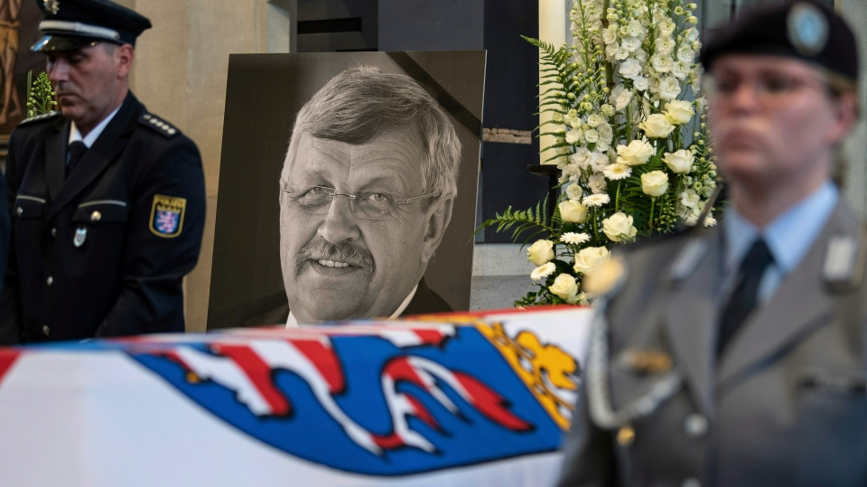 FILE-In this June 13, 2019 file photo a picture of Walter Luebcke stands behind his coffin during the funeral service in Kassel, Germany. (Swen Pfoertner/dpa via AP)
