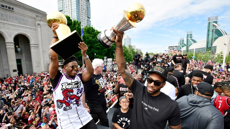 Toronto Raptors guard Kyle Lowry, left, holds the Larry O'Brien Championship Trophy as forward Kawhi Leonard holds his playoffs MVP trophy as they celebrate during the 2019 Toronto Raptors Championship parade in Toronto on Monday, June 17, 2019. (THE CANADIAN PRESS/Frank Gunn)