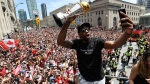 Toronto Raptors forward Kawhi Leonard takes a selfie holding his playoffs MVP trophy as he celebrates during the 2019 Toronto Raptors Championship parade in Toronto on Monday, June 17, 2019. THE CANADIAN PRESS/Frank Gunn