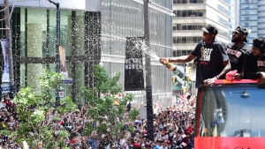 Toronto Raptors forward Pascal Siakam sprays the crowd with champagne as he celebrates during the 2019 Toronto Raptors Championship parade in Toronto on Monday, June 17, 2019. THE CANADIAN PRESS/Frank Gunn