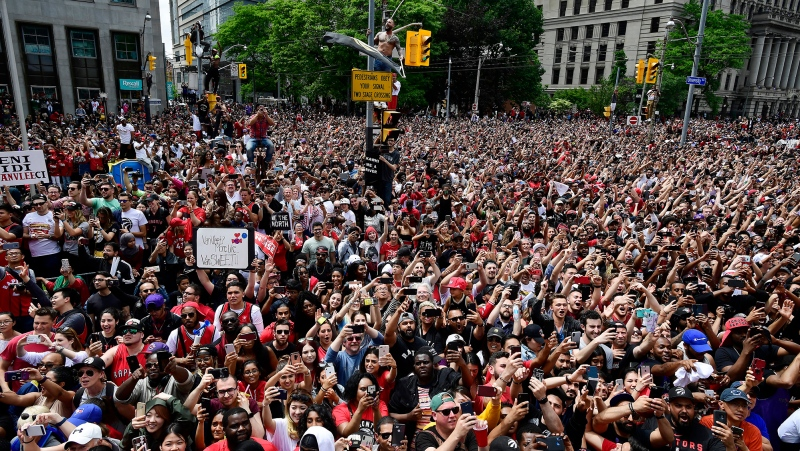 Fans line the streets and sit on street signs as they celebrate during the 2019 Toronto Raptors Championship parade in Toronto on Monday, June 17, 2019. THE CANADIAN PRESS/Frank Gunn