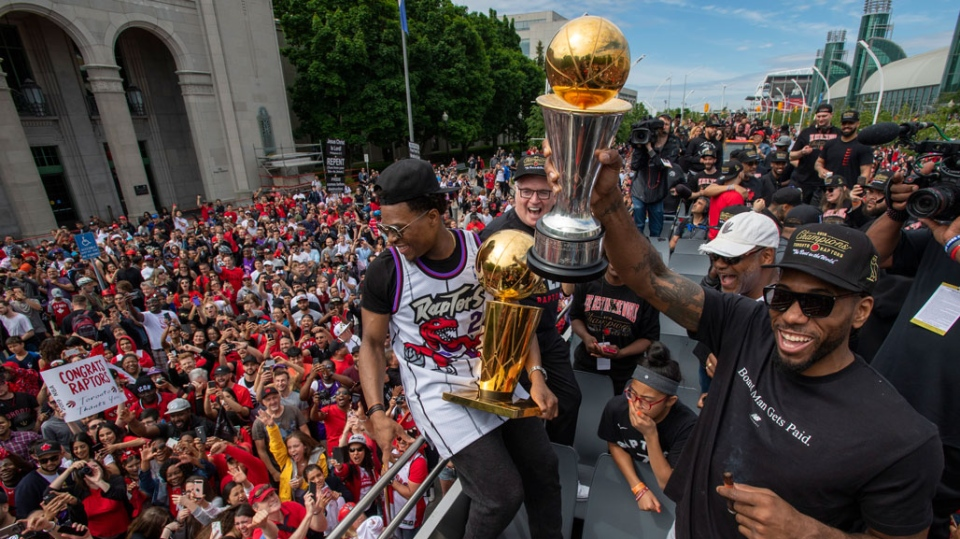 Toronto Raptors' Kawhi Leonard and Kyle Lowry hold up the trophies as they celebrate during the 2019 Toronto Raptors Championship parade in Toronto, on Monday, June 17, 2019. (THE CANADIAN PRESS/Frank Gunn)