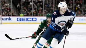 In this April 2, 2019, file photo, Winnipeg Jets defenseman Jacob Trouba (8) has the puck while shorthanded against Minnesota Wild center Luke Kunin (19) during the second period of an NHL hockey game in St. Paul, Minn. (AP Photo/Hannah Foslien, File)
