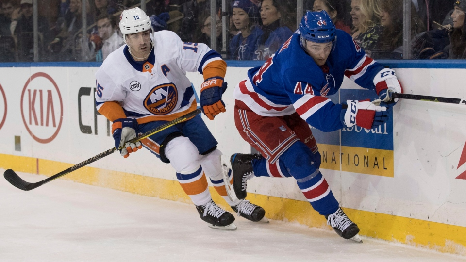 In this Jan. 10, 2019, file photo, New York Rangers defenseman Neal Pionk (44) and New York Islanders right wing Cal Clutterbuck (15) chase the puck during the first period of an NHL hockey game in New York. (AP Photo/Mary Altaffer, File)