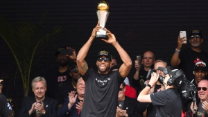 Toronto Raptors forward Kawhi Leonard hoists the MVP trophy next to teammates during the 2019 Toronto Raptors Championship parade in Toronto, on Monday, June 17, 2019.THE CANADIAN PRESS/Nathan Denette