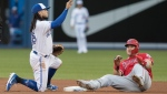 Los Angeles Angels' Mike Trout, right, is tagged out stealing second base by Toronto Blue Jays' Freddy Galvis during fourth inning American League MLB baseball action in Toronto, Monday, June 17, 2019. THE CANADIAN PRESS/Fred Thornhill