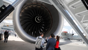 Visitor watch a jet engin propulsion of an Airbus 350-1000 at Paris Air Show, in Le Bourget, east of Paris, France, Monday, June 17, 2019. (AP Photo/Michel Euler)