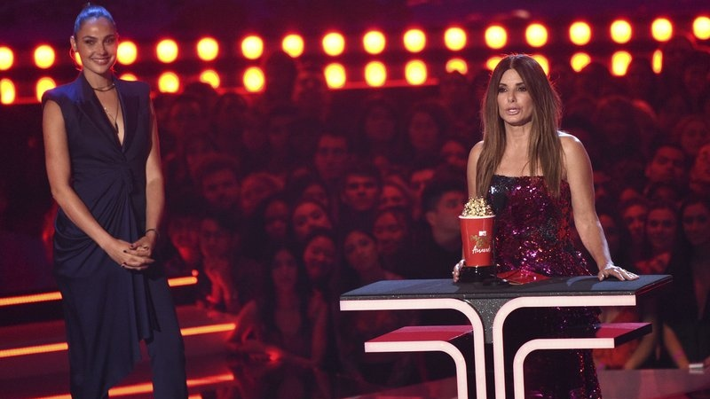 """Sandra Bullock accepts the award for most frightened performance for """"Bird Box"""" as presenter Gal Gadox looks on at the MTV Movie and TV Awards on Saturday, June 15, 2019, at the Barker Hangar in Santa Monica, Calif. (Photo by Chris Pizzello/Invision/AP)"""