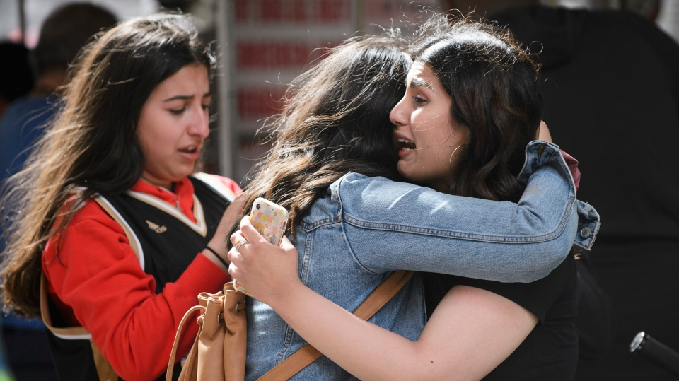 Friends embrace after shots were fired during the 2019 Toronto Raptors Championship parade in Toronto, on Monday, June 17, 2019. THE CANADIAN PRESS/Andrew Lahodynskyj
