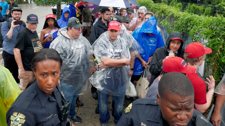 Supporters line up after a light rain before the gates open up to attend a campaign rally where U.S. President Donald Trump will formally announce his 2020 re-election bid Tuesday, June 18, 2019, in Orlando, Fla. (AP Photo/John Raoux)