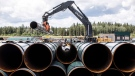 Pipe for the Trans Mountain pipeline is unloaded in Edson, Alta. on June 18, 2019. (THE CANADIAN PRESS/Jason Franson)