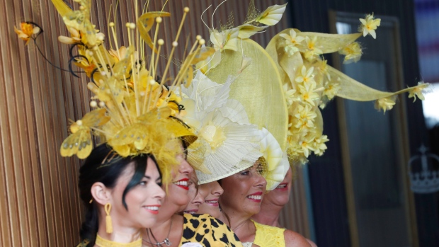 Racegoers pose for photographers as they arrive on the second day of the annual Royal Ascot horse race meeting in Ascot, England, Wednesday, June 19, 2019. (AP Photo/Alastair Grant)