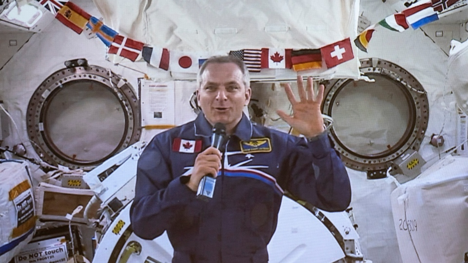Canadian Space Agency astronaut David Saint-Jacques waves goodbye at the end of his last press conference in orbit before returning to Earth on June 24, seen on a giant screen in Saint-Hubert, Que. on Wednesday, June 19, 2019. THE CANADIAN PRESS/Paul Chiasson