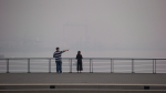 A man and woman look out at the harbour as smoke from wildfires burning in the province fills the air, in Vancouver on August 20, 2018. (THE CANADIAN PRESS/Darryl Dyck)