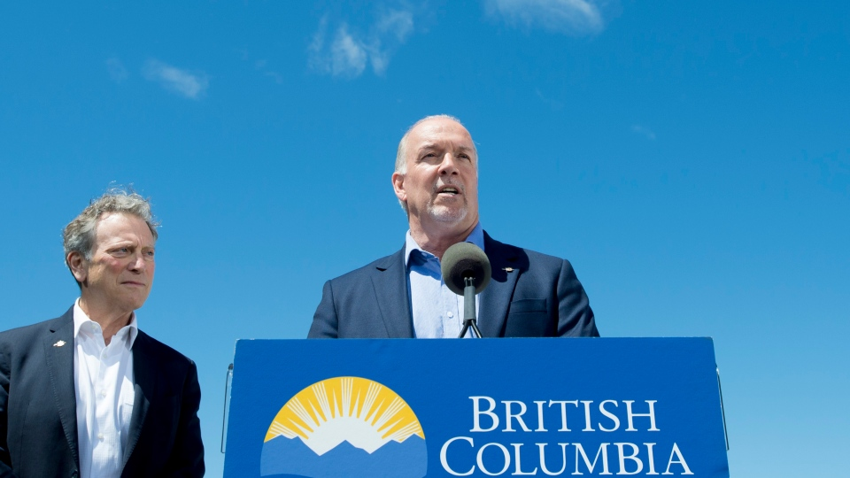 British Columbia Premier John Horgan and Minister of Environment and Climate Change George Heyman speak to the media regarding the Trans Mountain Pipeline during a news conference in downtown Vancouver, Tuesday June, 18, 2019. THE CANADIAN PRESS/Jonathan Hayward