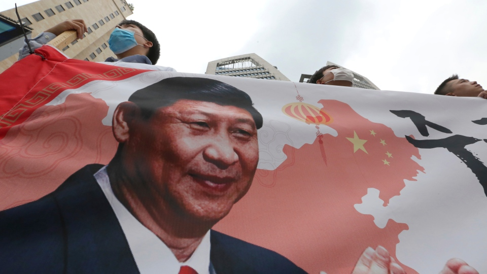 South Korean protesters with an image of Chinese President Xi Jinping stage a rally to denounce South Korean government's policy on China near the Chinese Embassy in Seoul, South Korea, Wednesday, June 19, 2019. (AP Photo/Ahn Young-joon)