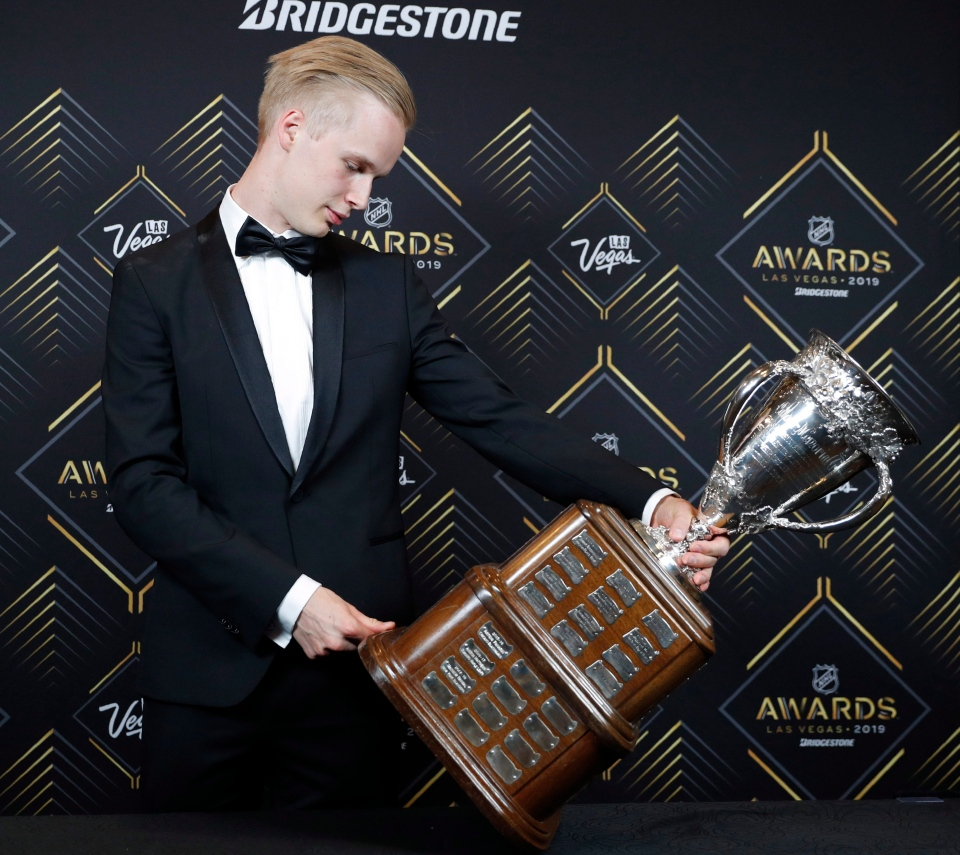 Vancouver Canucks' Elias Pettersson looks at the Calder Memorial Trophy after winning the honor at the NHL Awards, Wednesday, June 19, 2019, in Las Vegas. (AP Photo/John Locher)