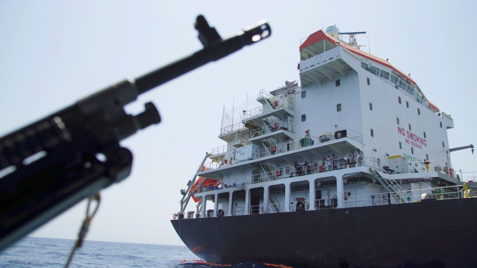 Sailors stand on deck above a hole the U.S. Navy says was made by a limpet mine on the damaged Panama-flagged, Japanese owned oil tanker Kokuka Courageous, anchored off Fujairah, United Arab Emirates, during a trip organized by the Navy for journalists, Wednesday, June 19, 2019. (AP Photo/Fay Abuelgasim)