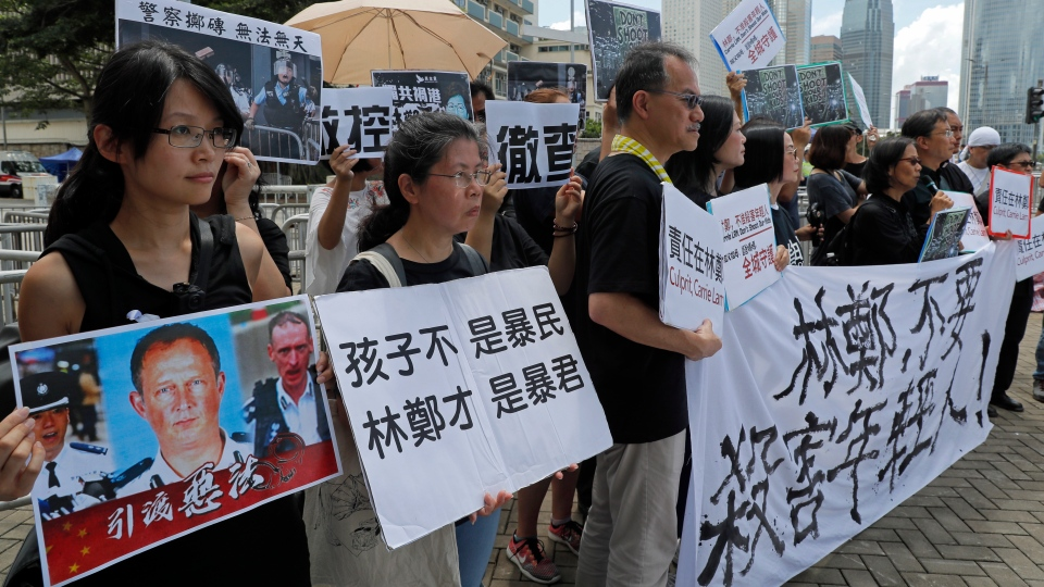 """Activists from various groups including parents and religious hold placards of picture of police commander with Chinese reads """"The child is not rioter, Carrie Lam is the tyrant"""", outside the government office demanding to stop shooting their kids in Hong Kong, Thursday, June 20, 2019. (AP Photo/Kin Cheung)"""