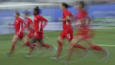 In this image taken with a slow shutter speed Canadian players warm up before the start of the Women's World Cup Group E soccer match between Canada and New Zealand in Grenoble, France, on June 15, 2019. (Francisco Seco / AP)