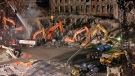 Workers and heavy machinery continue the cleanup and recovery effort in front of the remaining facade of 1 World Trade Center at Ground Zero in New York City on Nov. 7, 2001. (AP Photo / Stephen Chernin, File)