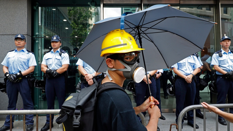 A protestor stands in front of a line of policemen outside the police headquarters in Hong Kong on Friday, June 21, 2019. (AP Photo/Vincent Yu)