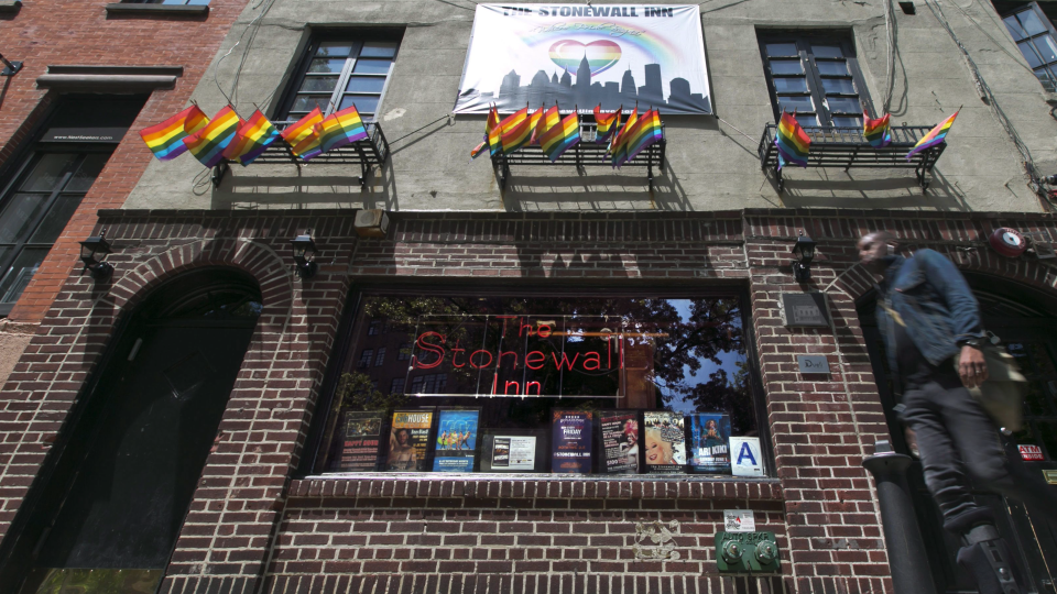 In this May 29, 2014 file photo, a man passes The Stonewall Inn in New York's Greenwich Village. (AP Photo/Richard Drew, File)