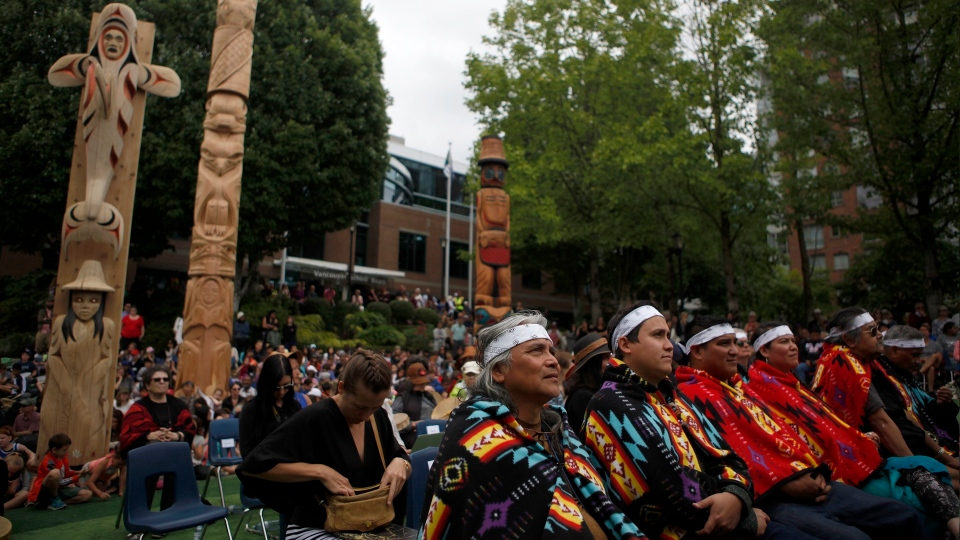Pole carvers and artists, right, look on as one Reconciliation Pole and two Welcome Figures are unveiled during a ceremony in honour of truth and reconciliation on National Indigenous Peoples Day at the Vancouver School District in Vancouver, B.C., on Friday, June 21, 2019. (THE CANADIAN PRESS/Chad Hipolito)