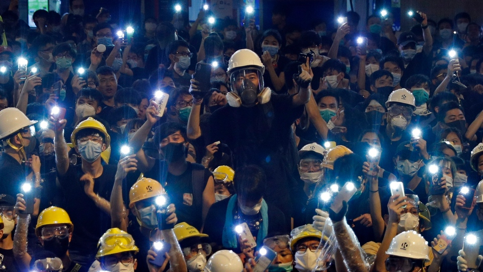 Protesters hold up the mobile phone lights in front of police headquarters in Hong Kong, Friday, June 21, 2019. (AP Photo/Vincent Yu)