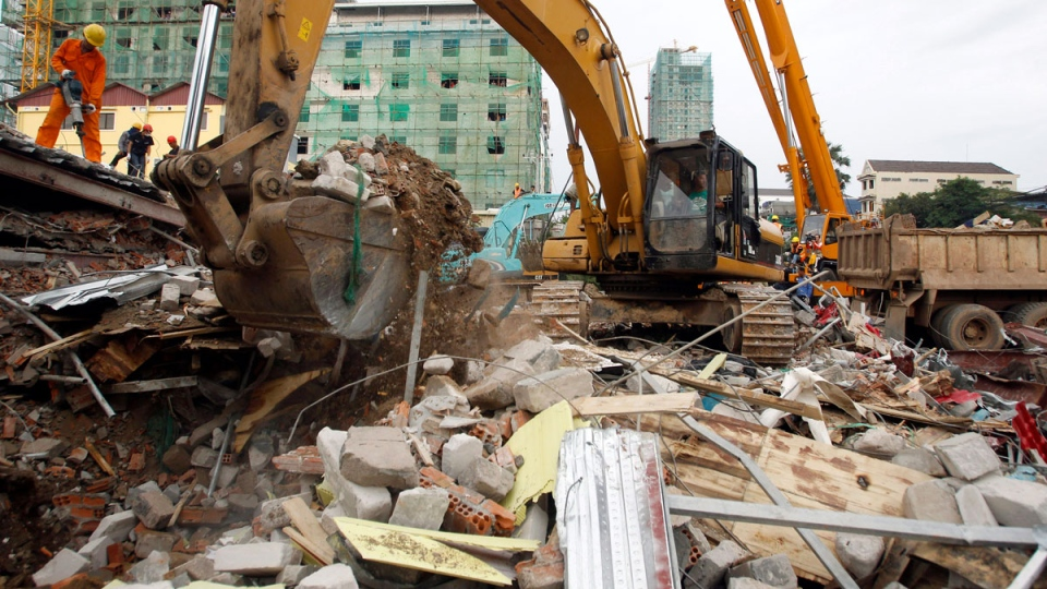 An excavator removes the rubble at the site of a collapsed building in Preah Sihanouk province, Cambodia, Saturday, June 22, 2019. (AP Photo/Heng Sinith)