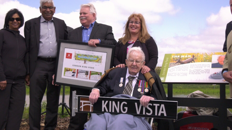 Gordon King holds the sign for King Vista, a street in the Keswick community that has been named in the veteran's honour.