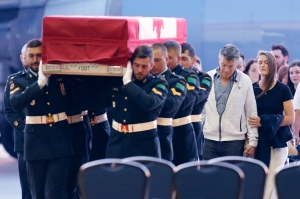 The body of Bombardier Patrick Labrie, a Canadian soldier who died in a parachute exercise in Bulgaria, is followed by his father Jean Labrie, left to right, and sister Veronique Labrie, as he arrives in Ottawa on Saturday, June 22, 2019. THE CANADIAN PRESS/ Patrick Doyle