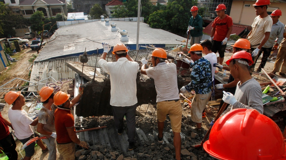 Rescuers try to remove the rubble at the site of a collapsed building in Preah Sihanouk province, Cambodia, Sunday, June 23, 2019. (AP Photo/Heng Sinith)