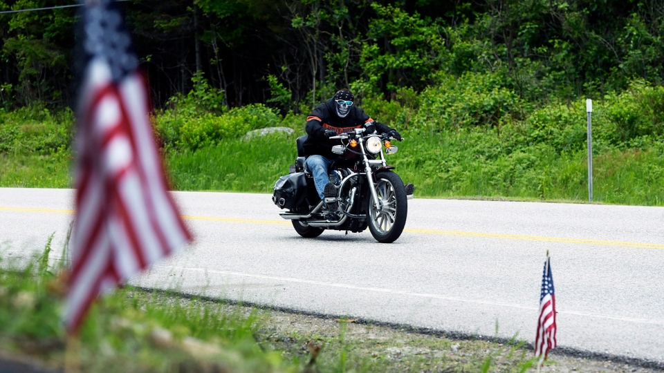 A motorcycle passes the scene of a fatal accident on Route 2 in Randolph, N.H., Saturday, June 22, 2019. (Paul Hayes/Caledonian-Record via AP)