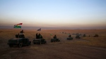 FILE - In this Oct. 17, 2016 file photo, a Kurdish Peshmerga convoy drives towards a frontline in Khazer, about 30 kilometers (19 miles) east of Mosul, Iraq. (AP Photo/Bram Janssen, File)