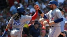 Toronto Blue Jays' Freddy Galvis, left, and Rowdy Tellez, right, celebrate after they scored on a single by teammate Danny Jansen in the sixth inning of a baseball game against the Boston Red Sox in Boston, Sunday, June 23, 2019. (AP Photo/Steven Senne)