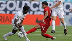 Cuba's Luis Paradela (23) tries to drives between Canada's Alphonso Davies (12) and Samuel Piette (6) during the first half of their CONCACAF Gold Cup soccer match in Charlotte, N.C., Sunday, June 23, 2019. (AP Photo/Chuck Burton)