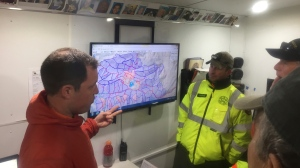 This April 17, 2017, photo provided by Michael St. John shows search and rescue volunteer and SARTopo creator Matt Jacobs, left, and search and rescue volunteers Mike Russo, center, and Bob Gehlen, right, in Sierraville, California, as they consult a SARTopo map while making plans to search for a missing aircraft. (Michael St. John/Marin County Sheriff's SAR unit via AP)