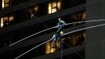 Aerialists Nik Wallenda, top, steps over his sister Lijana as they walk on a high wire above Times Square, Sunday, June 23, 2019, in New York. (AP Photo/Jason Szenes)