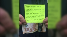 A person holds a $100 dollar bill and a note in this undated handout photo. The treasure was found by New Glasgow town employee Doug Miller while setting up for a funding announcement over the weekend. (THE CANADIAN PRESS/HO, Geralyn MacDonald)