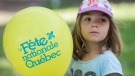 A young girl holds a balloon during Saint-Jean-Baptiste day celebrations in Montreal, Monday, June 24, 2019. THE CANADIAN PRESS/Graham Hughes