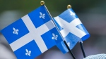 A woman wears miniature Quebec flags on her hat during Saint-Jean Baptiste day celebrations in Montreal, Monday, June 24, 2019. THE CANADIAN PRESS/Graham Hughes