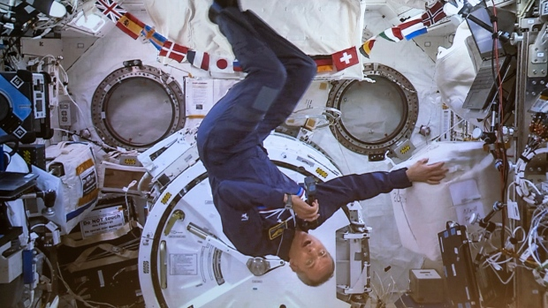 Canadian Space Agency astronaut David Saint-Jacques turns upside-down during his last press conference in orbit before returning to Earth on June 24, seen on a giant screen in Saint-Hubert, Que. on Wednesday, June 19, 2019. THE CANADIAN PRESS/Paul Chiasson
