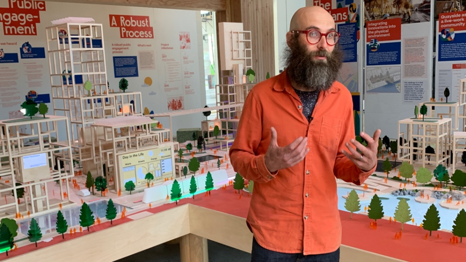 Sidewalk Labs' director of public realm Jesse Shapins speaking in front of a replica of the firm's proposal neighbourhood for the Toronto waterfront. (Matt Talbot / CTVNews.ca)