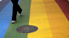 A woman walks across a rainbow crosswalk in support of the LGBT community at the intersection of 13th and Locust streets, Thursday, June 25, 2015, in Philadelphia. (AP / Matt Slocum)